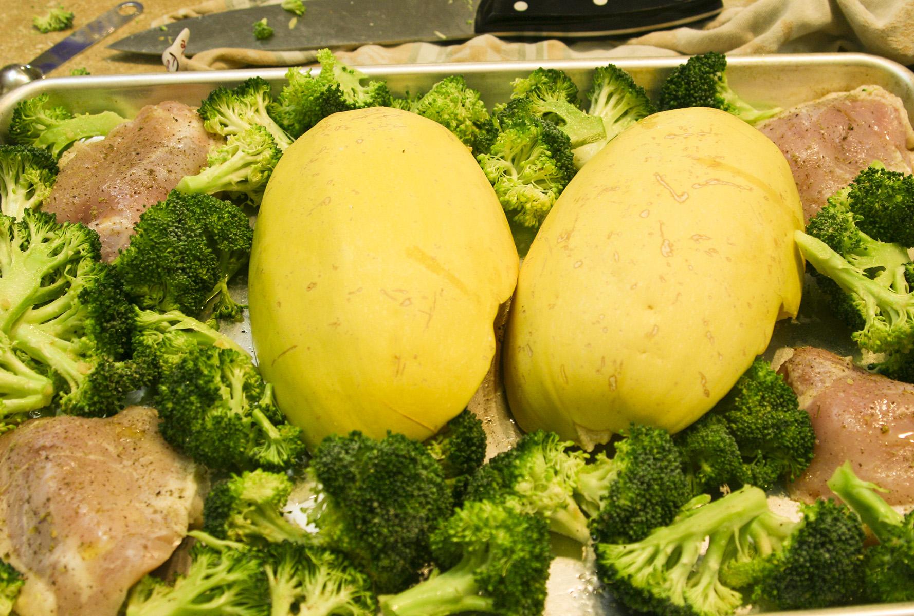 spaghetti squash broccoli and chicken on a baking sheet pan