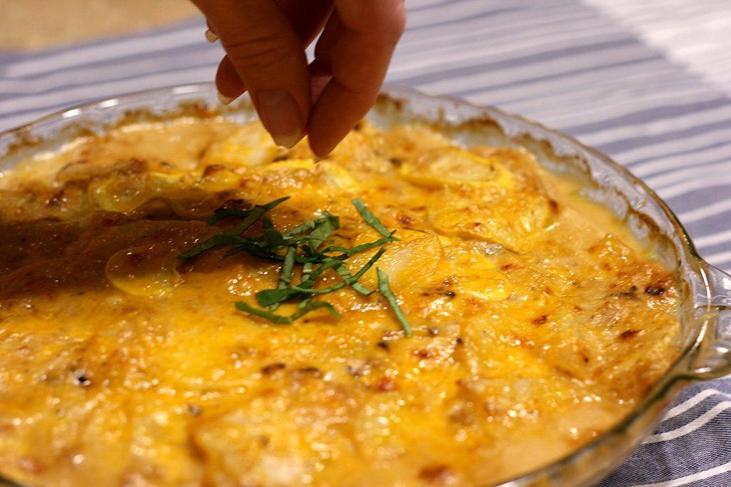 sprinkling basil on top of potato and yellow squash au gratin