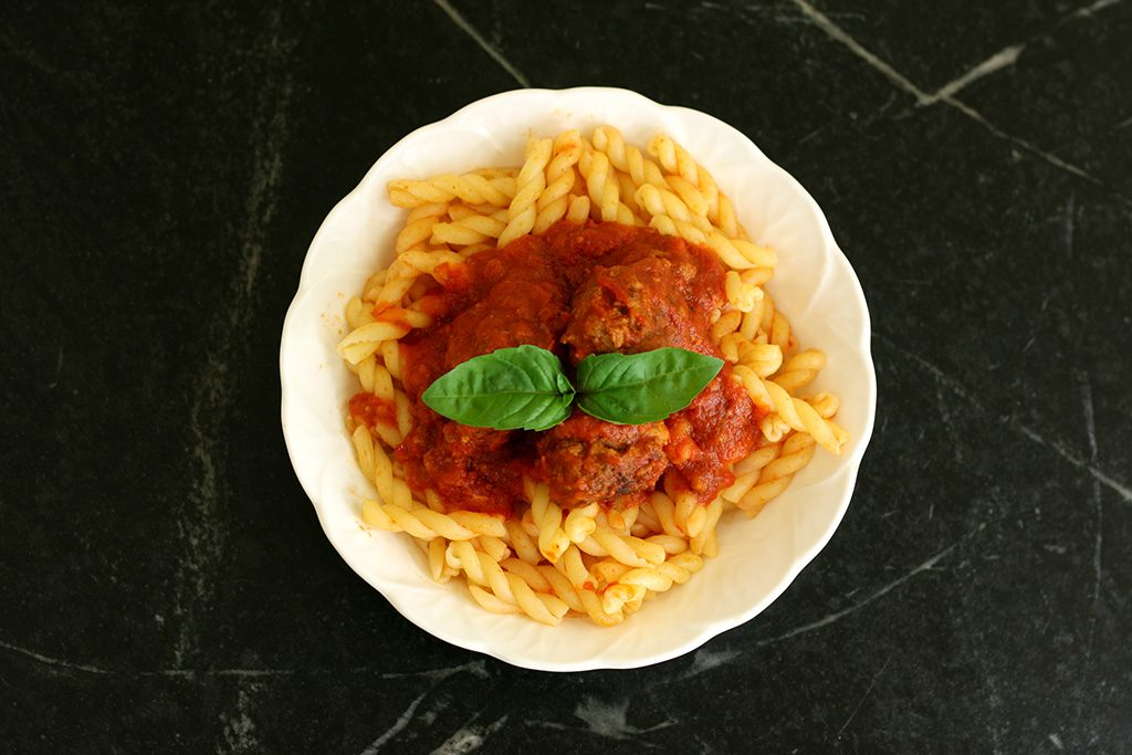 Italian Meatballs and sauce over pasta in a bowl.