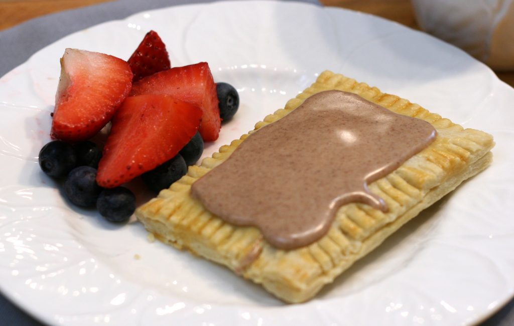 Brown sugar and cinnamon toaster pastry with fruit on a plate.