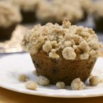 banana muffin with streusel crumb topping on a plate