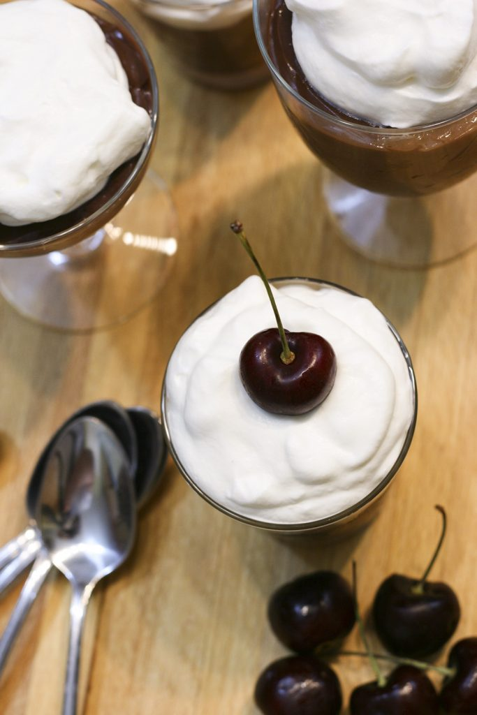 chocolate pudding with whipped cream and cherry on top